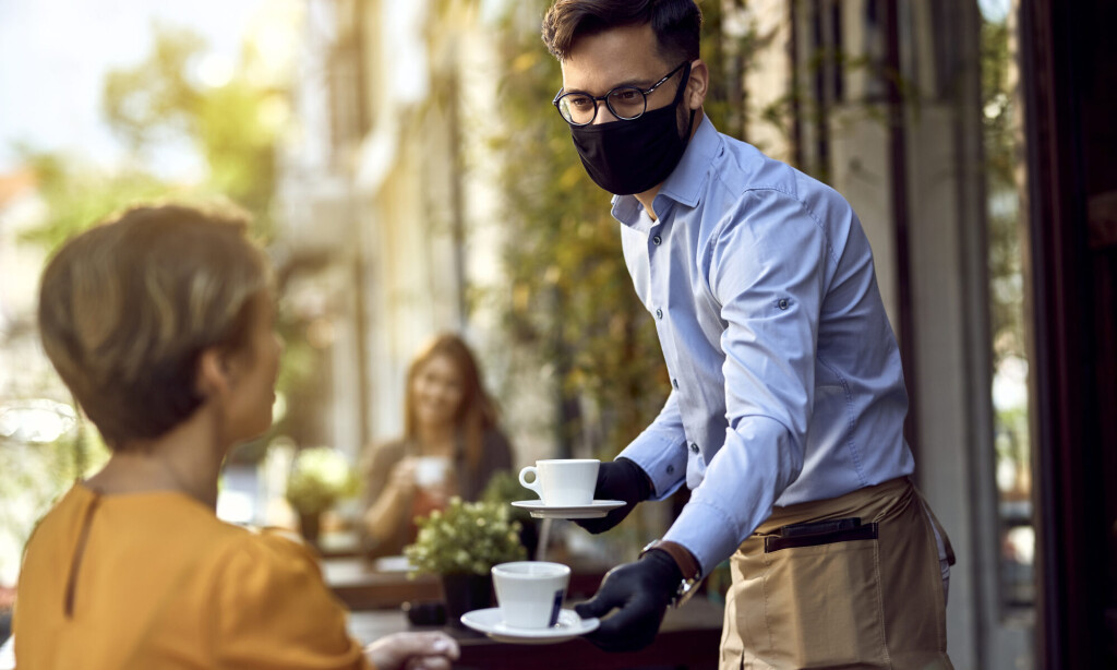 Waiter serving coffee to female guest while wearing protective face mask.